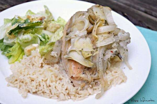 Lemon Artichoke Crock Pot chicken recipe on a white plate with rice and Caesar salad