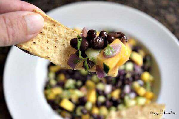 This black bean and mango salad recipe inside a white bowl with a hand holding a chip up close with the salad on the end of it