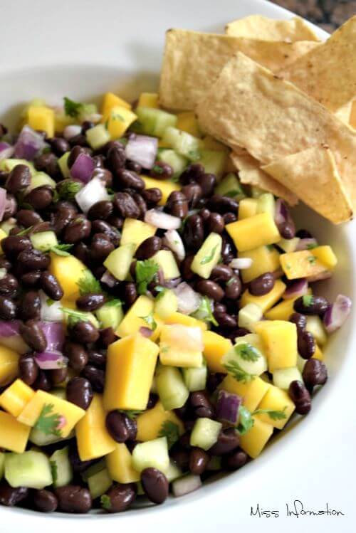 black bean and mango salad recipe in a white bowl with tortilla chips on the side