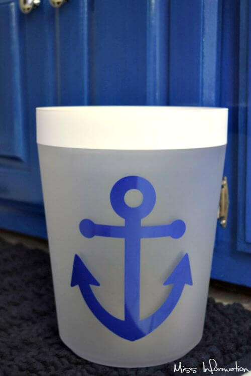 A plain white trashcan from Target decorated with vinyl for a nautical theme