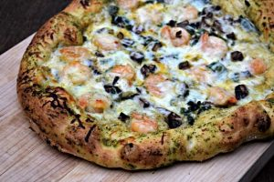 Shrimp Scampi Pizza topped with pesto, creamy alfredo sauce, spinach mushrooms and melted cheese is a gourmet dinner that takes 10 minutes to put together.